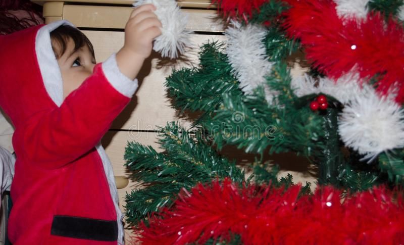 Toddler putting christmas decoration on christmas tree royalty free stock photography