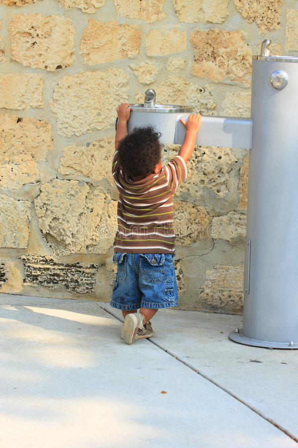 Toddler Reaching for Water. Young toddler reaching for the water fountain stock photo