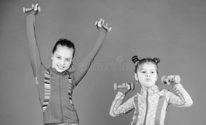 Toddler repeat exercise after sister. Sport exercises for kids. Healthy upbringing. Sporty babies. Following her sister. Girls cute kid exercising with royalty free stock image