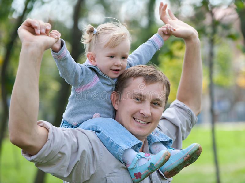 Toddler riding her dad in the park stock photography