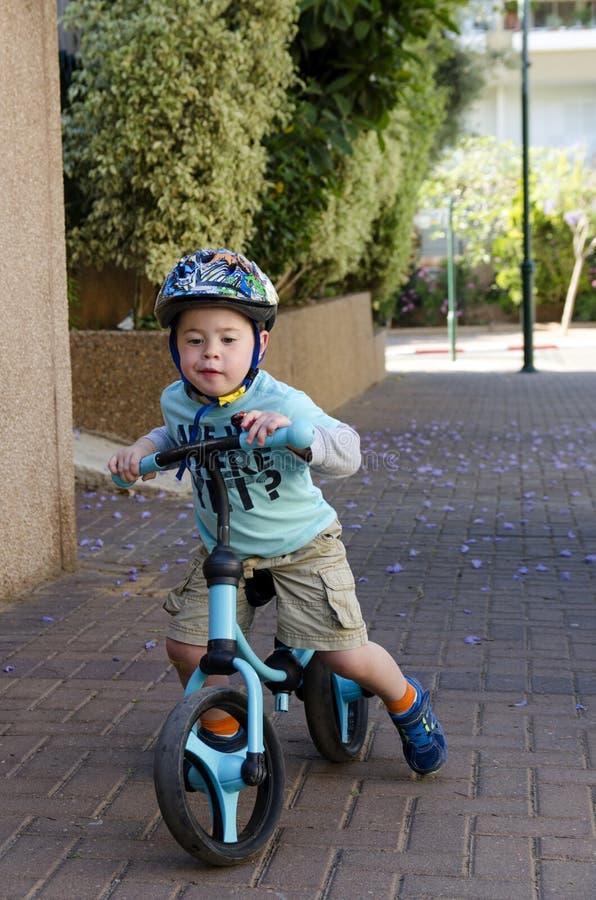 Toddler riding on his balance bicycle stock image
