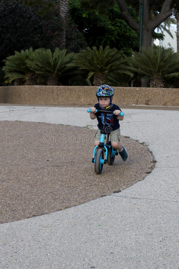 Toddler riding on his balance bicycle stock photography