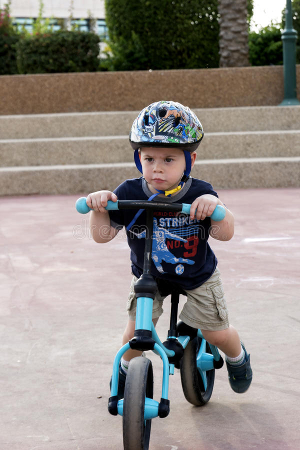 Toddler riding his balance bicycle stock photography