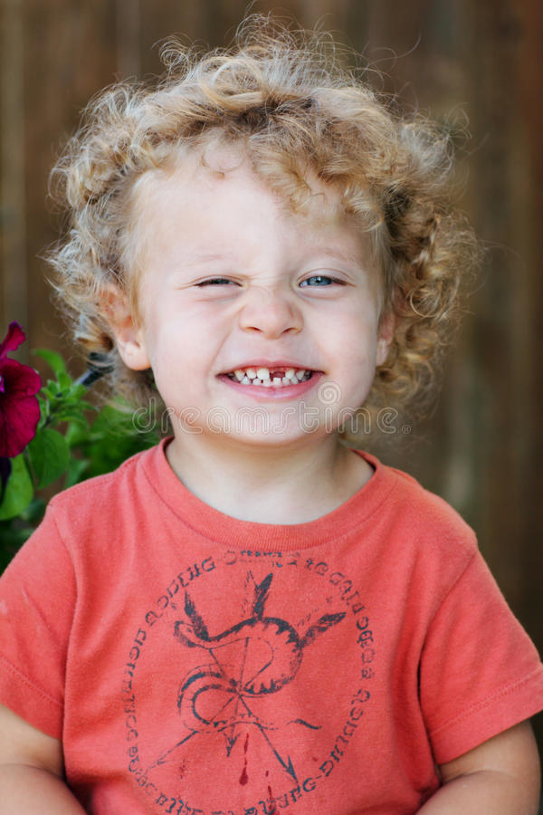 Toddler with ringlets & missing tooth. A closeup of a cute toddler with curly blond ringlets missing a tooth. Shallow DOF stock images