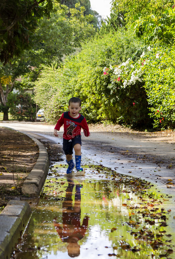 Toddler running in a puddle with his new boots royalty free stock image