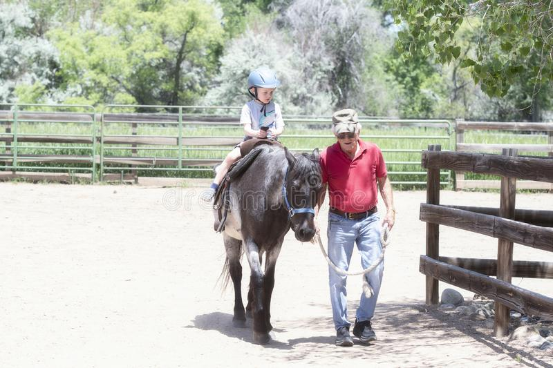 Toddler with a Safety Helmet on Goes on a Pony Ride at a Local Farm with his Horse Being Led Grandfather. Toddler with a Safety Helmet on Goes on a Pony Ride at royalty free stock photos