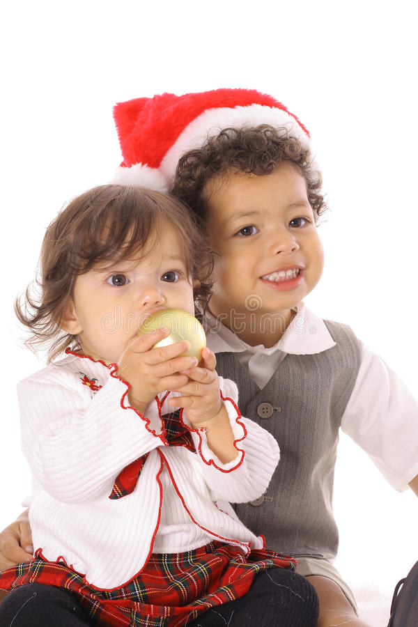 Toddler in santa hat with sister stock images