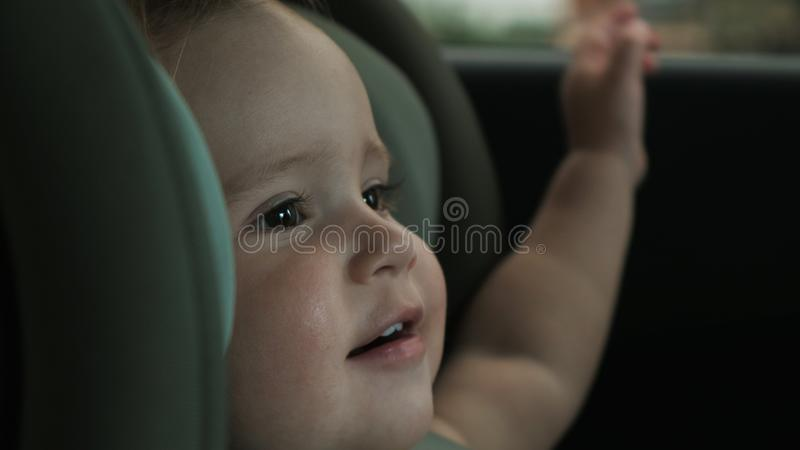 Toddler sits in child car safety seat and looks out window stock photography