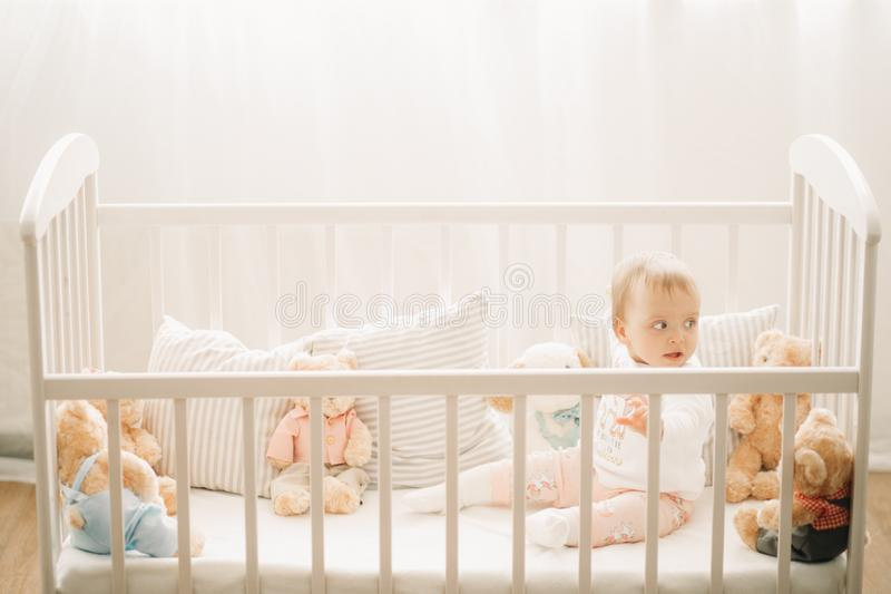 The toddler sits in a crib and plays. Among pillows and teddy bears royalty free stock photos