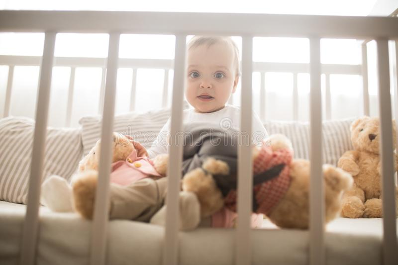 The toddler sits in a crib and plays. Among pillows and teddy bears royalty free stock image