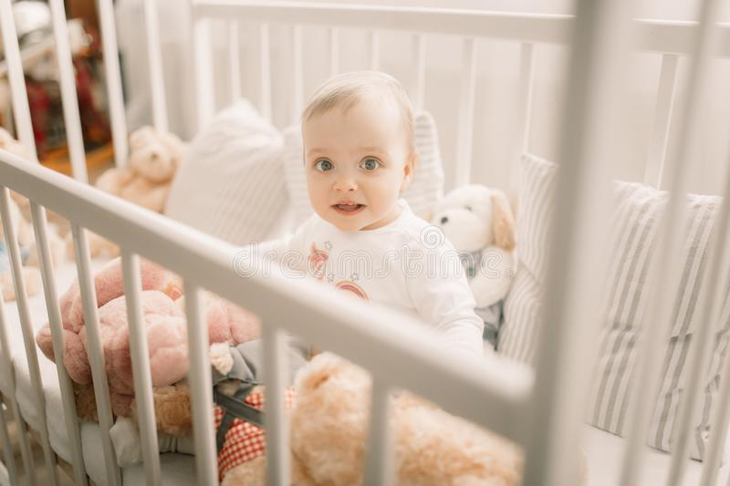 The toddler sits in a crib and plays. Among pillows and teddy bears stock image