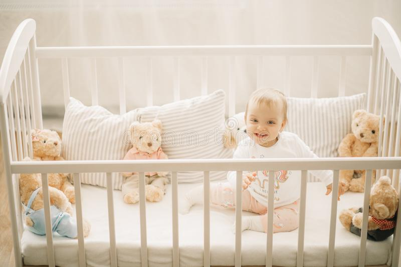 The toddler sits in a crib and plays. Among pillows and teddy bears stock photography