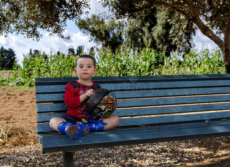 Toddler sitting on a bench holding his bicycle helmet royalty free stock images