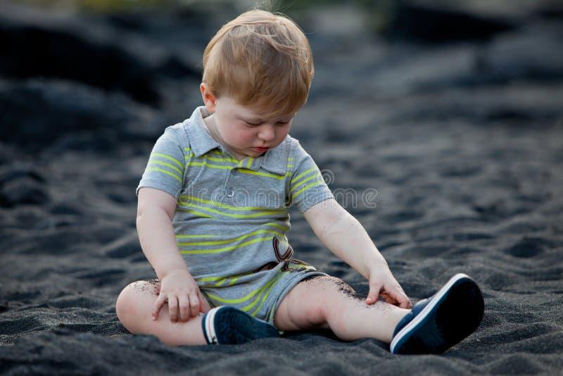 Download Toddler Sitting On Black Sand Beach Stock Photo - Image: 20179824