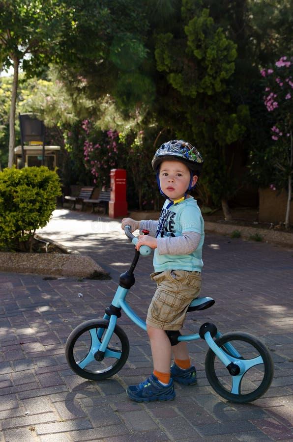Toddler sitting on his balance bicycle royalty free stock photo