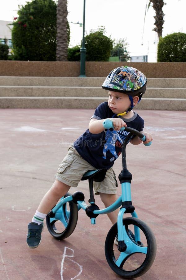 Toddler sitting on his balance bicycle stock photo
