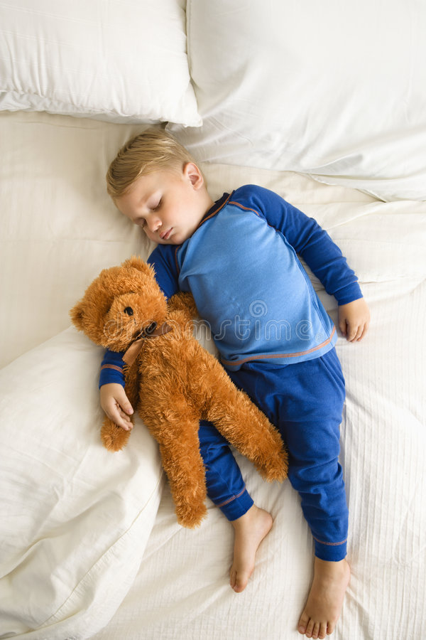 Toddler sleeping with bear. stock photo