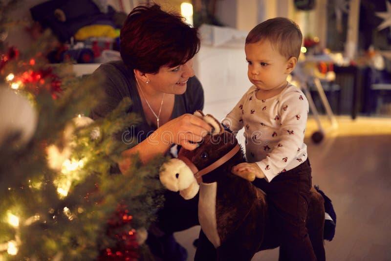 Toddler speelde met zijn paardenspeelgoed bij de kerstboom royalty-vrije stock fotografie