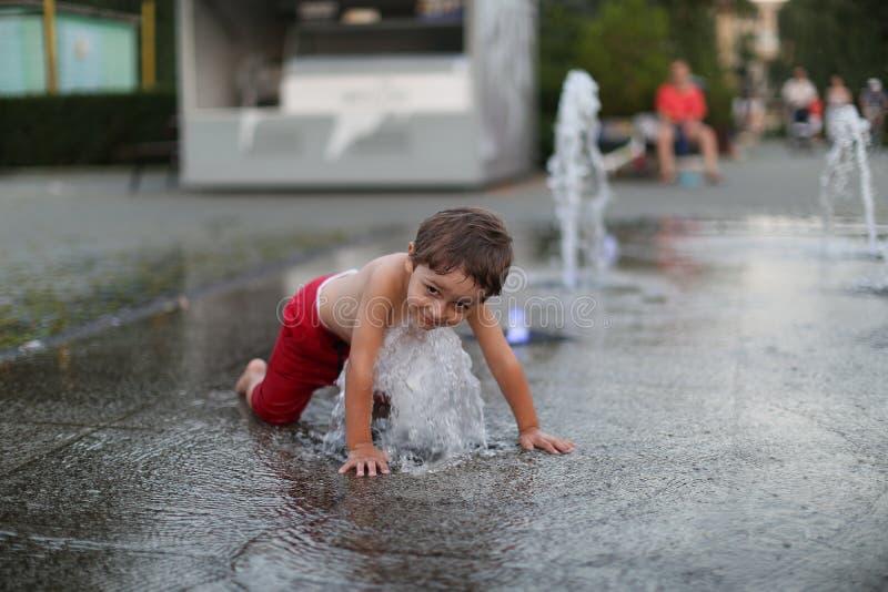 Toddler and a splashing water fountain stock photos