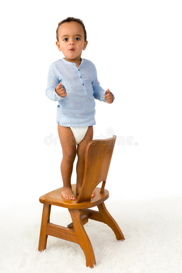 Toddler standing on chair royalty free stock images