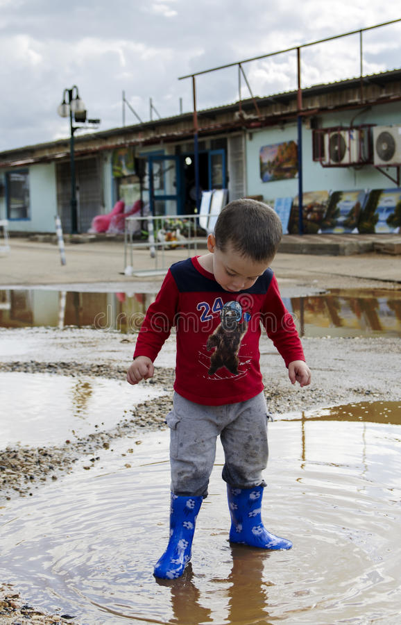 Toddler standing in a puddle with his new boots royalty free stock photo