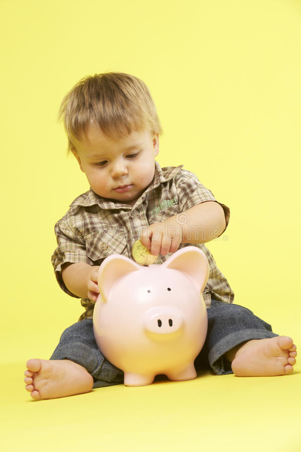 Toddler In Studio With Piggy Bank stock images