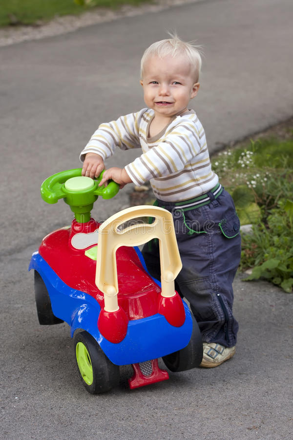 Toddler with toy. Toddler playing with his toy tractor stock photos