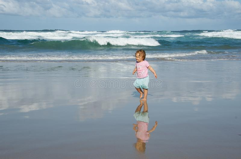 Toddler walking on beach stock photos