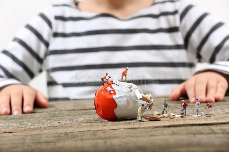 Toddler watching miniature people breaking an egg. Boy toddler watching miniature people breaking a chocolate egg, under construction site stock image