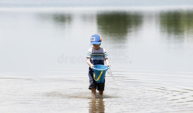 Toddler wearing a Hat & Sunglasses Walks in a Lake Near Shore Hauling Water for Sand Castles. With a Bucket stock images