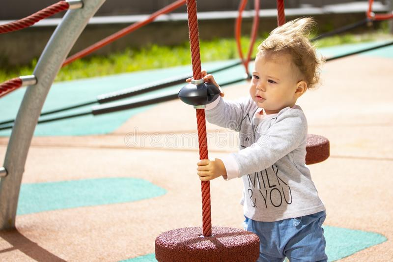 Toddler 1 year girl boy Caucasian, child play on the playground, baby with wavy hair in the wind, horizontal summer royalty free stock photo