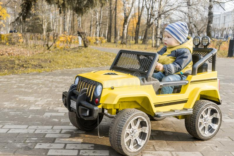 Toddler on yellow children drive car with an electric motor in autumn Park stock image