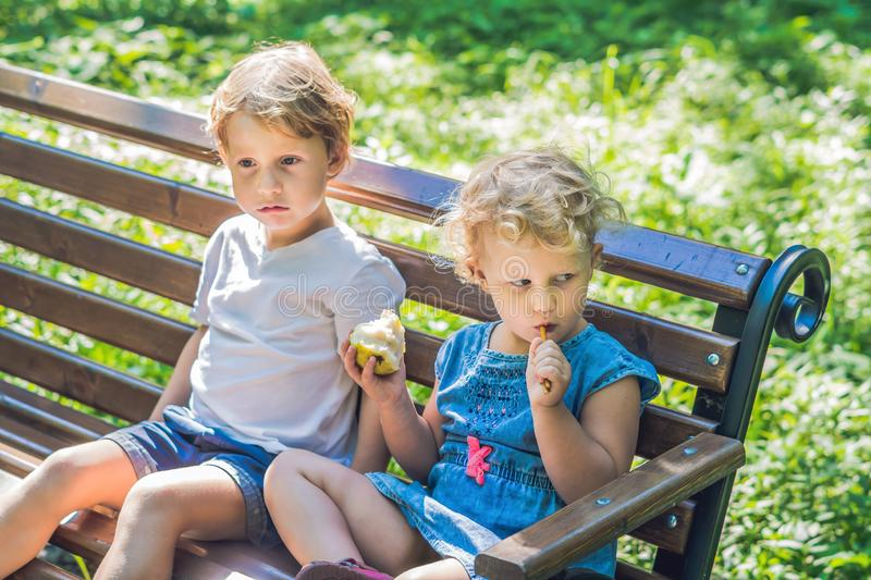 Toddlers boy and girl sitting on a bench by the sea and eat an apple royalty free stock photo