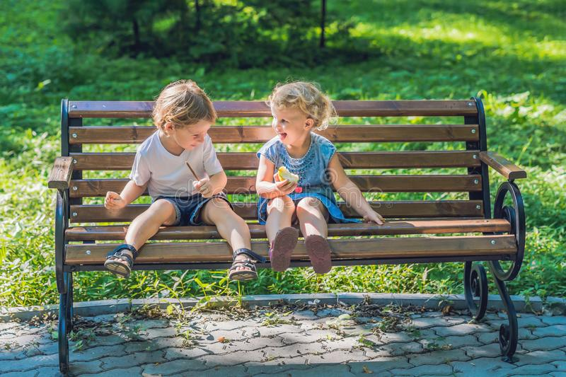 Toddlers boy and girl sitting on a bench by the sea and eat an apple royalty free stock photos