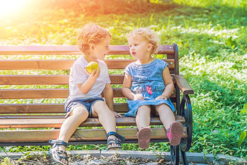 Toddlers boy and girl sitting on a bench by the sea and eat an apple royalty free stock images