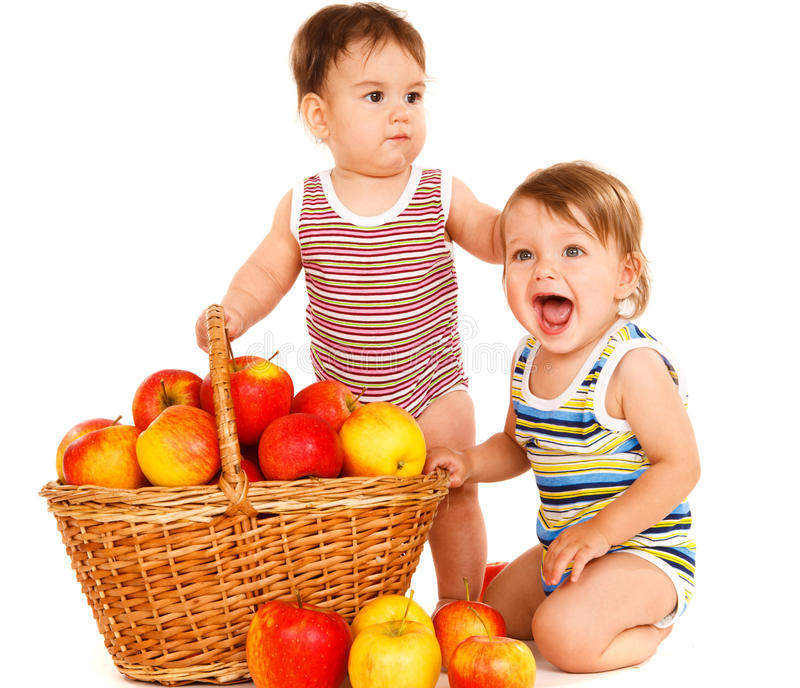 Toddlers with fruit basket. Two sweet toddlers and a fruit basket stock images