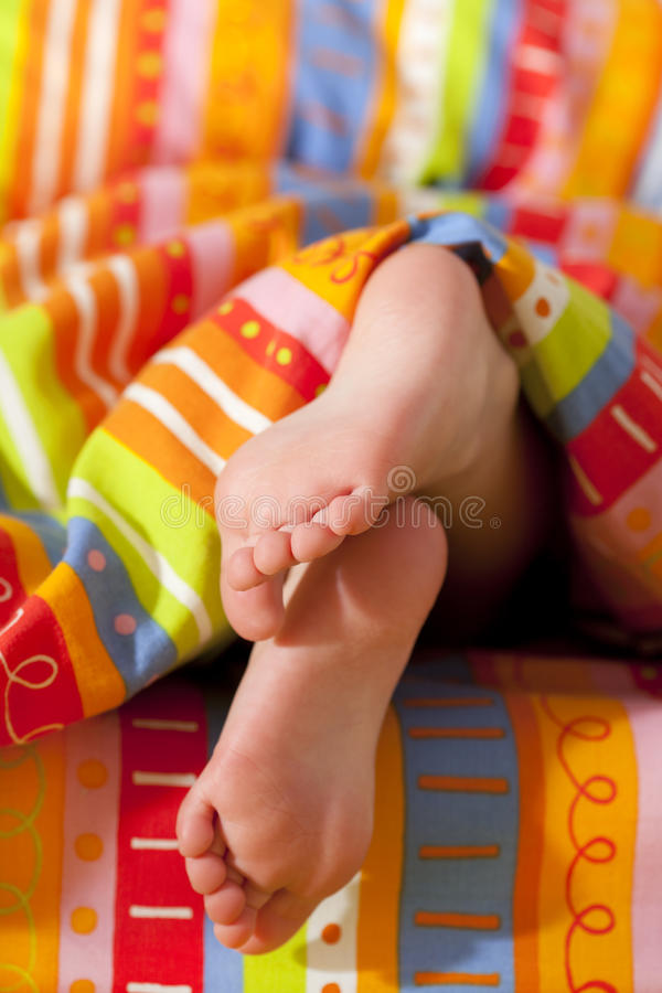 Toddlers girl feet in a bed under the morning sun stock photo