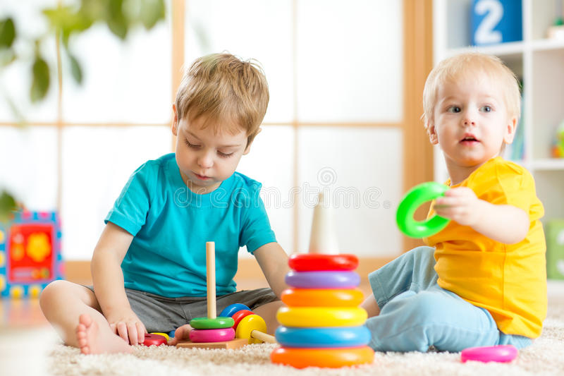 Toddlers kids playing with wooden blocks at home. Toddlers kids playing with wooden blocks on floor at home stock photo
