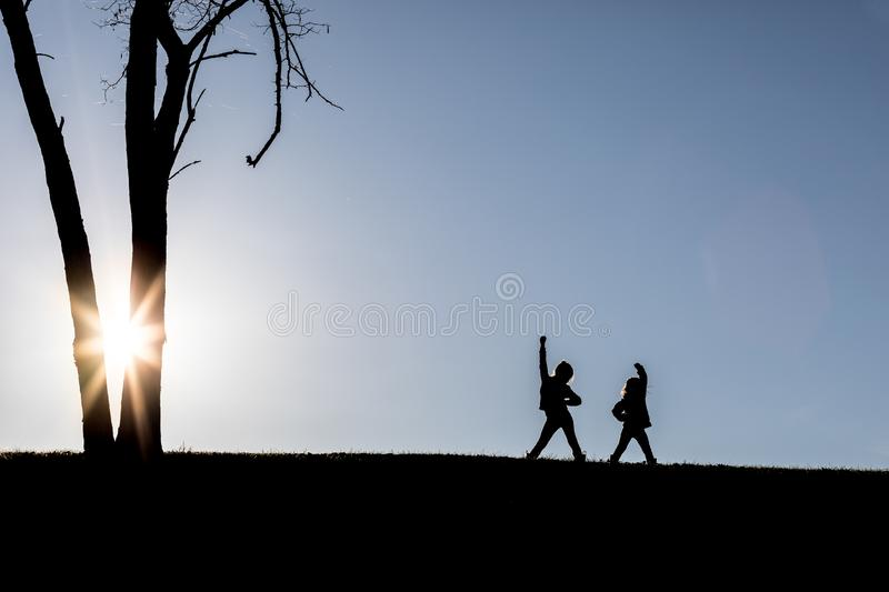 Toddlers playing on a hill with the sun behind them. Striking a power pose stock image