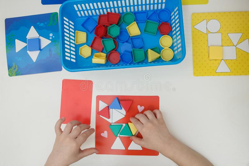 Toddlers playing multicolored educational games, mosaic and puzzles table.  stock photo
