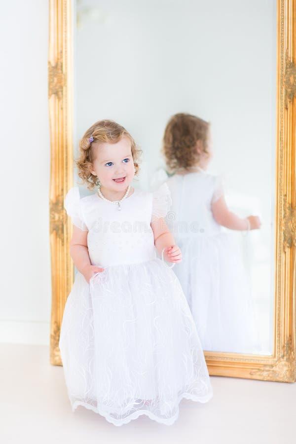 Toddlger flicka som framme försöker på den vita klänningen av spegeln arkivbilder