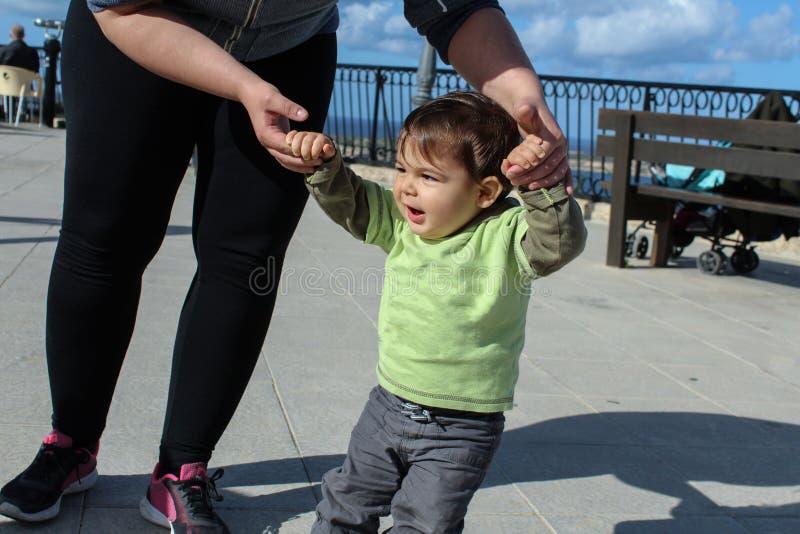 Todler di un anno che impara come camminare con la madre fotografia stock