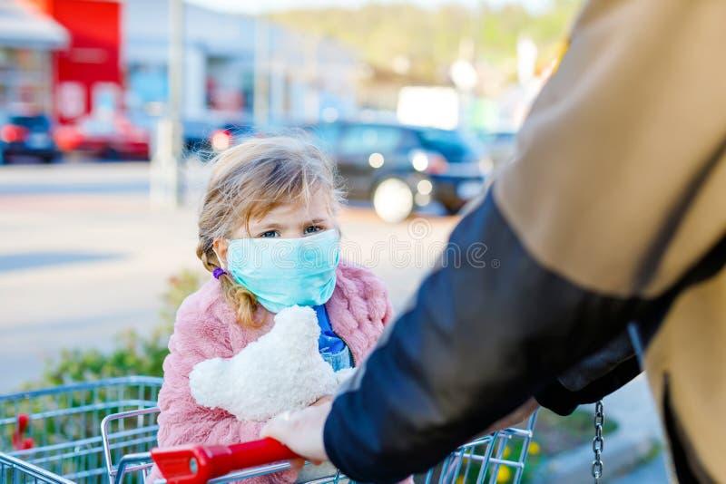 Todler girl in medisch masker als bescherming tegen een pandemische coronavirusziekte Cute child met behulp van beveiligingsappar stock foto's
