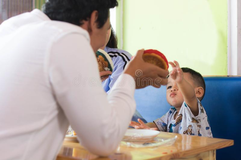 Todler playing cake with his father at cafe stock image