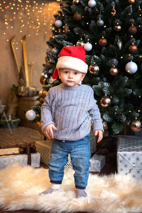 Todler-pojken klädd i jeans och en tröja och julhatt i närheten av den festilt dekorerade julgranen arkivbilder