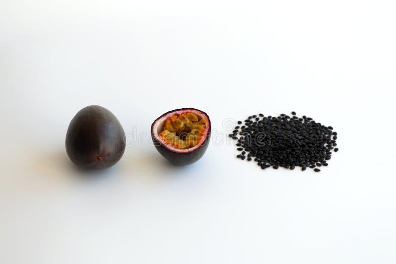 Todo do fruto de paixão, metade, e sementes pretas imagem de stock royalty free