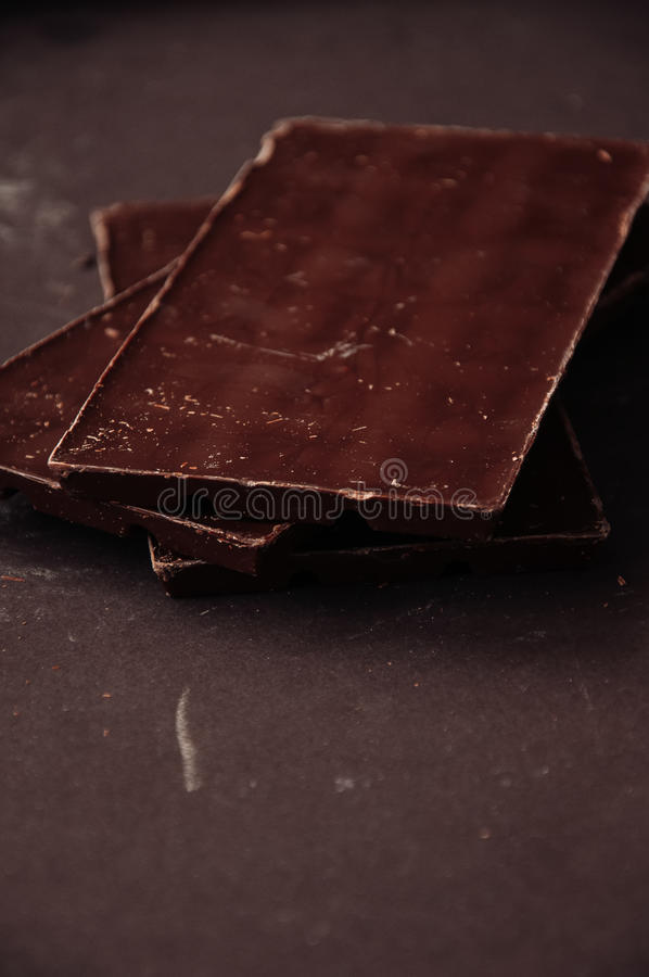 Todo e partes de barras de chocolate escuras em um darkbackground em imagens de stock