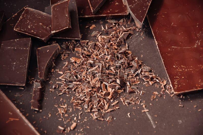 Todo e partes de barras de chocolate escuras em um darkbackground em foto de stock royalty free