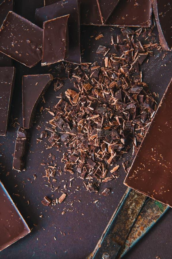 Todo e partes de barras de chocolate escuras em um darkbackground em foto de stock