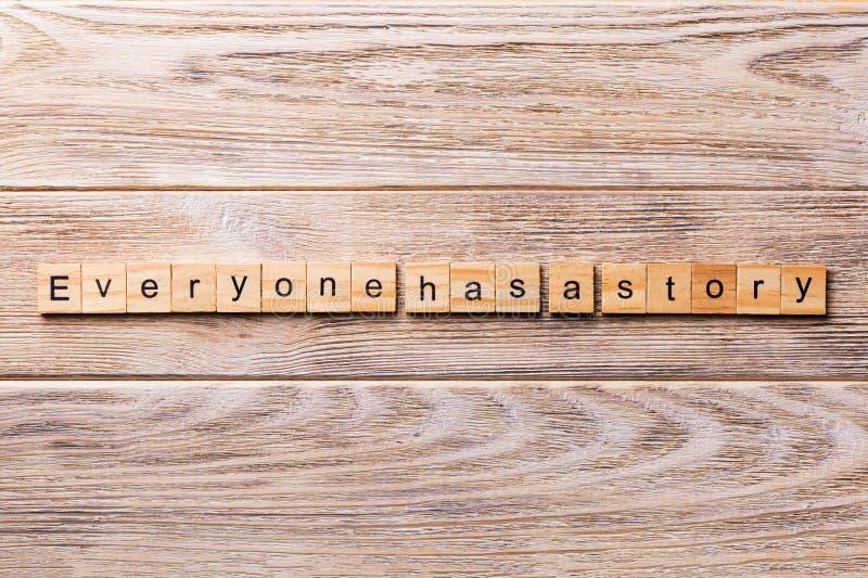 Todo el mundo tiene una palabra de la historia escrita en el bloque de madera Todo el mundo tiene un texto de la historia en la t foto de archivo libre de regalías